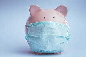 Piggy bank wearing medical mask over nose and mouth. Coronavirus concept.