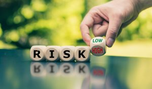 """Symbol for reducing a risk. Cubes form the word """"RISK"""" while a hand turns a cube and changes the word """"high"""" to low"""" (or vice versa)."""