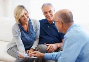 Happy senior couple smiling and listening to financial advisor at home
