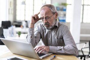 Worried senior businessman working on laptop in office, hand on head.