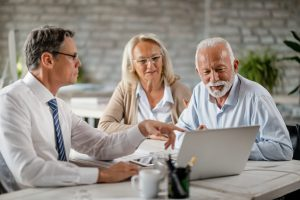 Senior couple using laptop with their financial advisor during a meeting in the office.