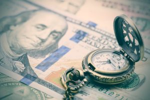 Vintage / retro color style : Classic pocket watch on a hundred US dollar bill